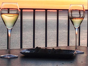 Two glasses of wine at sunset in Liguria
